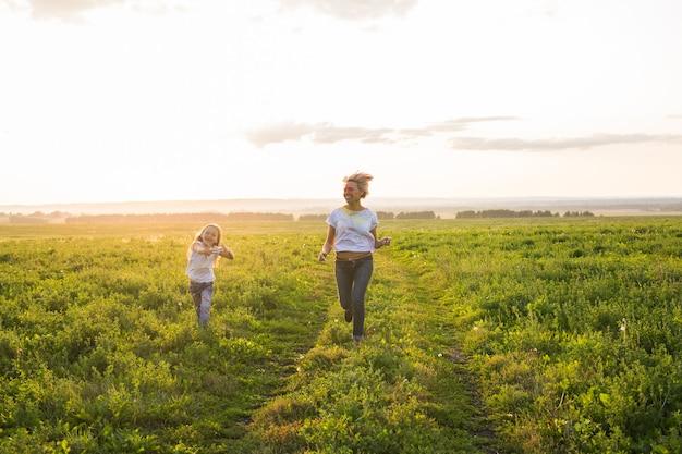 Concepto de familia, verano y vacaciones - pequeña hija y madre corren en el campo de verano