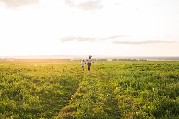 Concepto de familia, verano y vacaciones - pequeña hija y madre corren en el campo de verano.