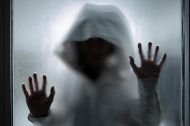 Concepto fantasma, persona con capucha detrás de un cristal.