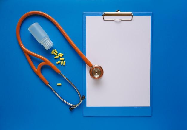 Concepto de farmacia. tabletas y estetoscopio sobre una mesa azul.