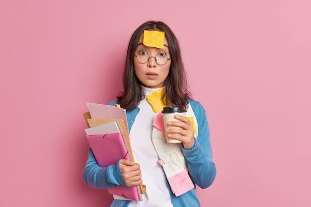Concepto de fecha límite y exceso de trabajo. aturdido oficinista asiática bebe café para llevar.