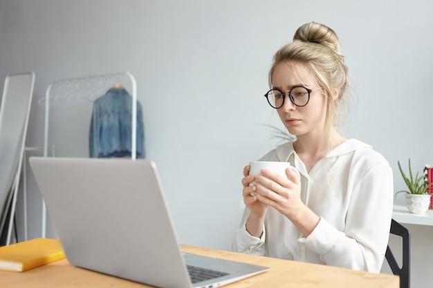 Concepto de fecha límite y exceso de trabajo. joven mujer caucásica independiente frustrada en elegantes gafas bebiendo otra taza de café mientras trabaja en un proyecto urgente, sentada frente a una computadora portátil abierta