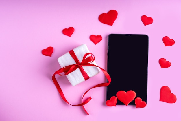 Concepto de felicitaciones en línea. pantalla de tableta o teléfono en blanco negro con forma de corazones rojos y regalo