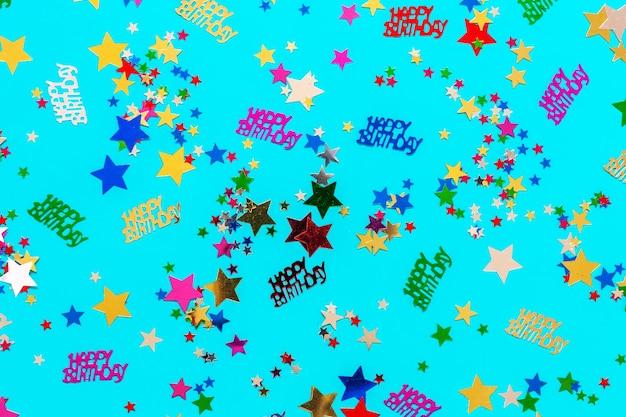 Concepto de feliz cumpleaños con confeti de brillo multicolor sobre fondo azul.