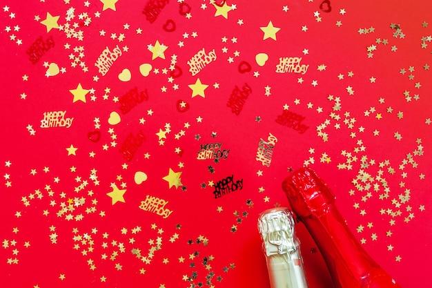 Concepto de feliz cumpleaños con confeti dorado brillo y botellas de champán sobre fondo rojo.