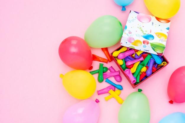 Concepto de feliz cumpleaños globos de colores y caja de regalo en una mesa rosa, diseño de vista superior