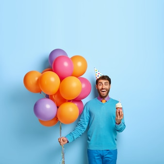 Concepto de feliz cumpleaños. sonriente hombre europeo tiene pastelito tasy