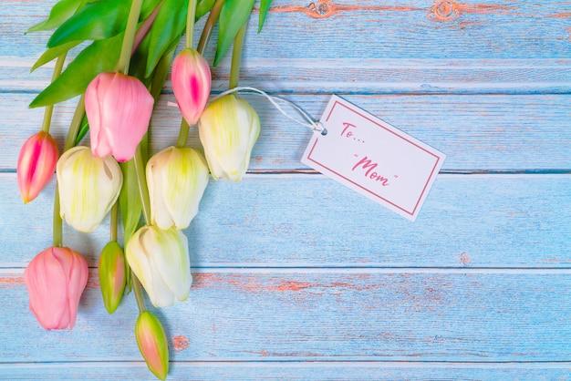 Concepto feliz del día de la madre con la etiqueta de la flor y del papel en la tabla de madera