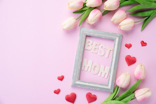 Concepto de feliz día de la madre. flor de tulipán rosa con corazón de papel y marco de fotos.