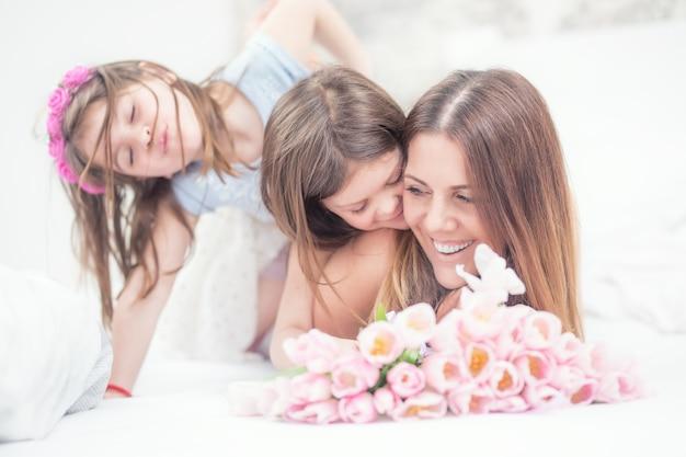 Concepto de feliz día de la madre. mamá con dos lindas hijas gemelas en la cama del dormitorio y un ramo de tulipanes de flores.
