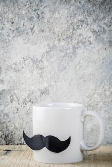 Concepto de feliz día del padre con taza de café como padre con bigote