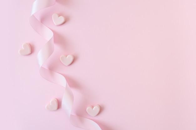 Concepto de feliz día de san valentín o día de la madre. cinta rosa y corazones sobre un fondo rosa