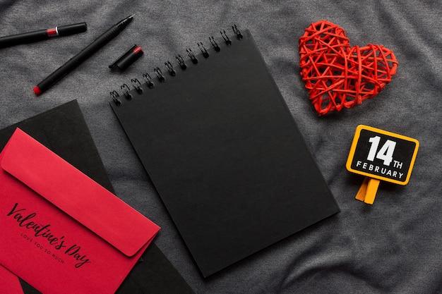Concepto feliz del día de tarjeta del día de san valentín, libro negro, corazón rojo y pluma en el paño gris