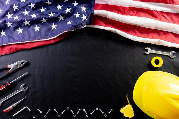 Concepto de feliz día del trabajo. bandera americana sobre fondo negro oscuro con diferentes herramientas de construcción.