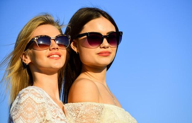 Concepto de feminidad. mujeres hermosas en el fondo del cielo azul del día soleado. hermandad y comunidad femenina. amistad femenina. poder femenino. moda de verano. encuentra la fuerza interior de la mujer. armonía y equilibrio.