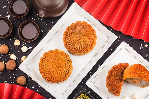 Concepto del festival del medio otoño, pasteles de luna tradicionales en mesa con taza de té.
