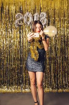 Concepto de fiesta de año nuevo con chica haciendo un selfie