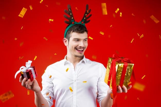 Concepto de fiesta de año nuevo feliz diversión sonriente encantador guapo hipster hombre chico masculino celebrando las vacaciones de navidad de invierno con sombrero de cuerno de ciervo con regalos caja de regalo confeti dorado