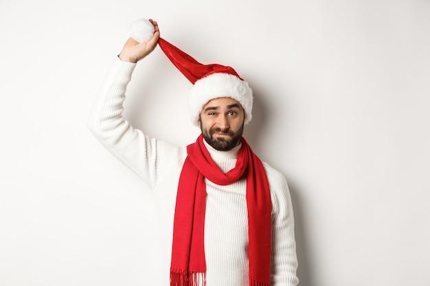 Concepto de fiesta y celebración de navidad. chico triste despegando el gorro de papá noel y haciendo muecas, mirando molesto, de pie contra el fondo blanco, mal año nuevo