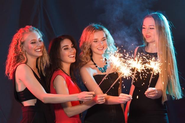 Concepto de fiesta, celebración y vacaciones de año nuevo - mujeres jóvenes alegres con bengalas encendidas.