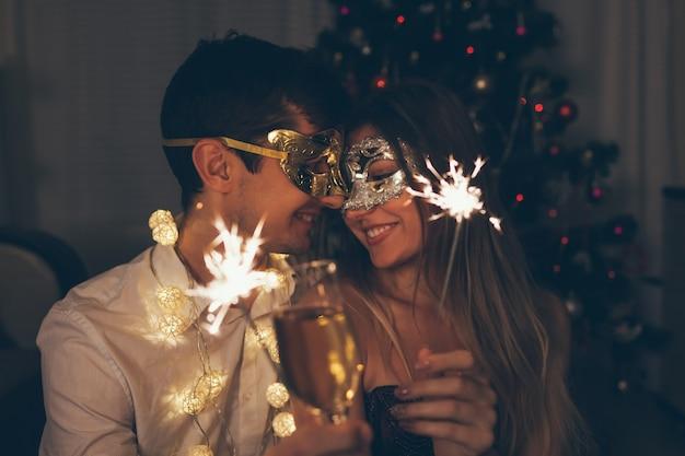 Concepto de fiesta de disfraces de navidad y año nuevo pareja quemando bengalas por árbol iluminado