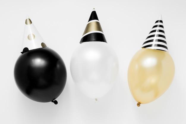 Concepto de fiesta de navidad. globos blancos, negros y dorados en sombreros de fiesta sobre fondo blanco. feliz año nuevo celebración