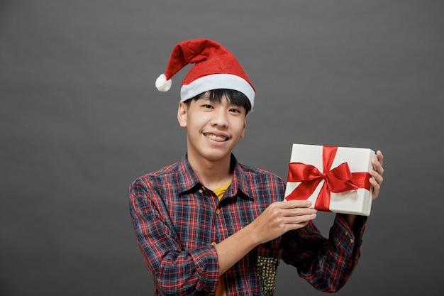 Concepto de fiesta y vacaciones de navidad. joven asiático con caja de regalo foto de estudio, aislado sobre fondo gris