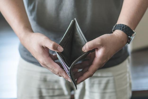 Concepto financiero de bancarrota. persona abre su billetera vacía sin dinero para pagar la deuda en pa