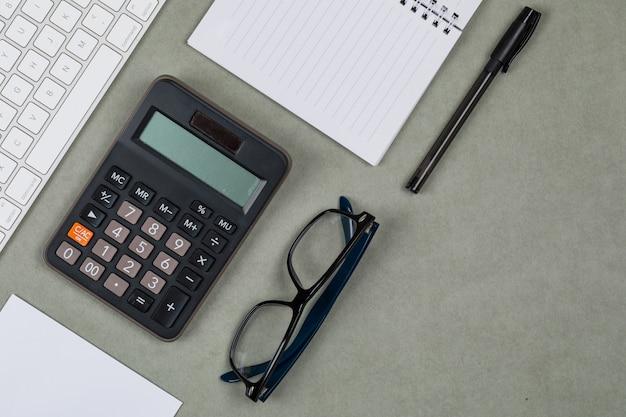 Concepto financiero con cuaderno, papel, bolígrafo, calculadora, teclado, gafas sobre fondo gris plano lay.