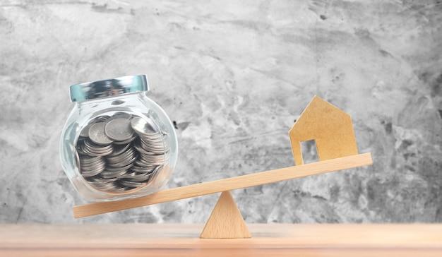 Concepto financiero de la hipoteca de la casa de inversión inmobiliaria, casa modelo y monedas de dinero que se equilibran en balancín