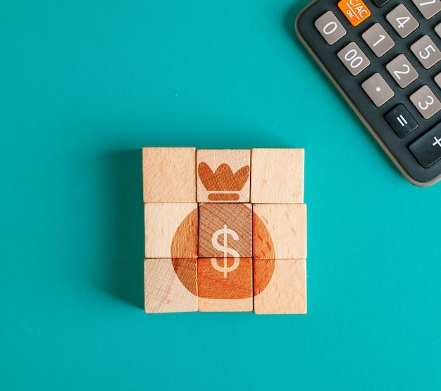 Concepto financiero con icono en cubos de madera, calculadora en mesa turquesa endecha plana.