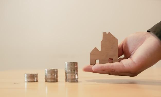 Concepto financiero de la inversión inmobiliaria y de la hipoteca de la casa, mano que pone el dinero pila de monedas con casa de madera