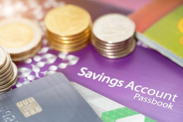 Concepto financiero, libretas de ahorro, tarjeta de crédito y moneda.