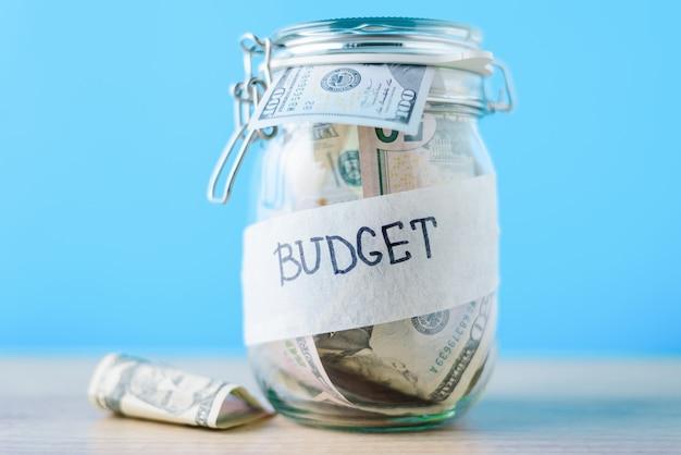 Concepto de finanzas e inversiones. banco de ahorro de vidrio con billetes de un dólar y presupuesto de inscripción sobre un fondo azul.
