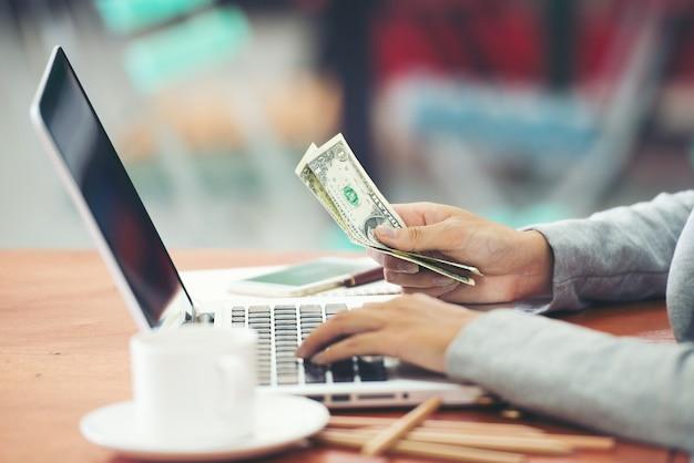 Concepto de las finanzas, de la economía y del negocio - cercano para arriba de feman con la computadora portátil que cuenta el dinero