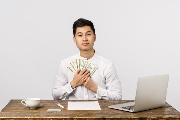 Concepto de finanzas, empresas y negocios. apuesto joven empresario chino exitoso en la oficina con computadora portátil, documentos acostado mesa, tenencia de dólares, mucho dinero en efectivo mucho dinero y sonriendo