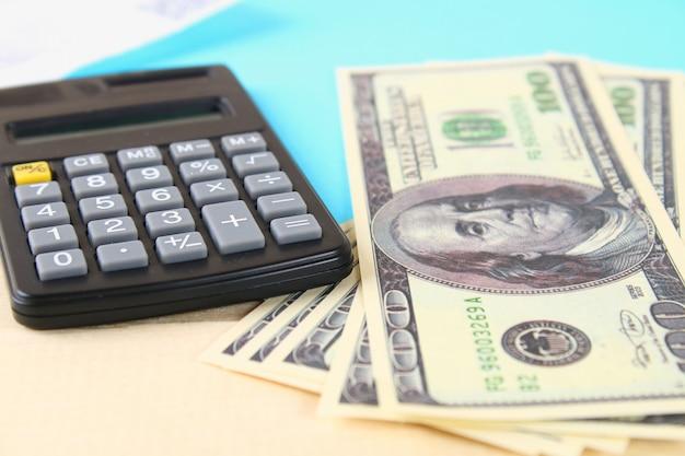 Concepto de finanzas: estados unidos billetes de cien dólares, calculadora, billetes.