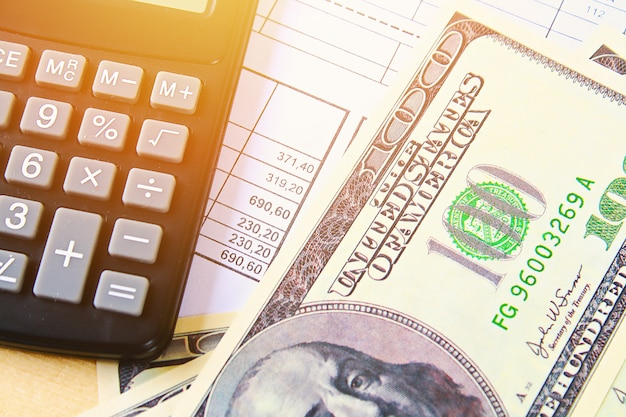 Concepto de finanzas. estados unidos billetes de cien dólares, calculadora, facturas.
