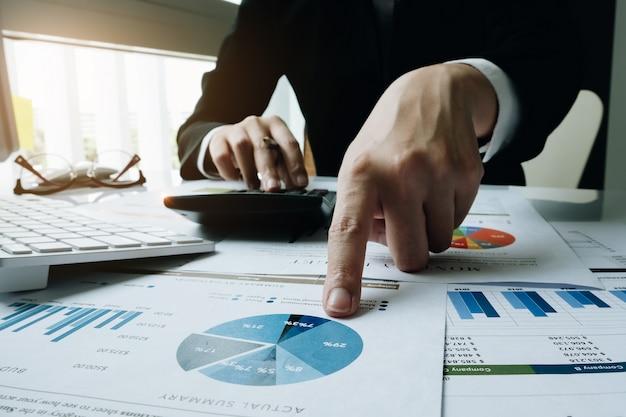 Concepto de las finanzas, pluma de tenencia de la empresaria usando la calculadora