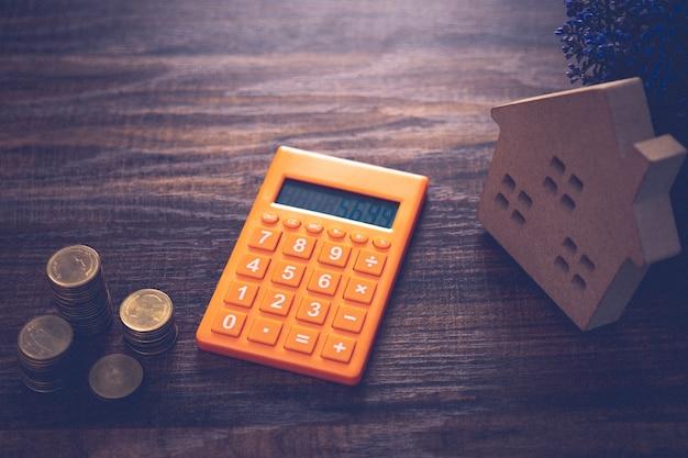 Concepto de finanzas del este real, apiladas de monedas de dinero con calculadora y modelo de madera en la mesa