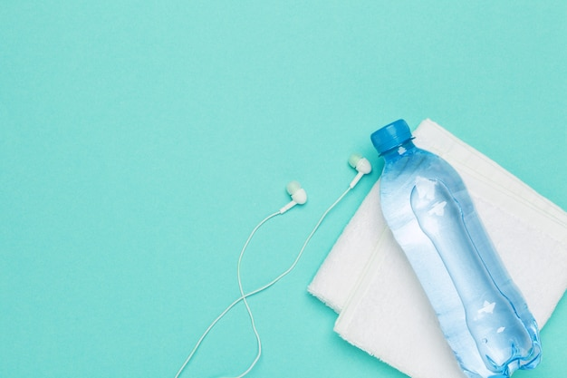 Concepto de fitness con botella de agua, teléfono móvil con auriculares