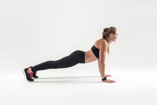 Concepto de fitness. cardio, ejercicio energético. mujer rubia haciendo flexiones de brazos. foto de estudio sobre fondo gris