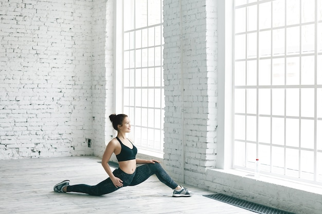 Concepto de fitness, deportes, energía, salud y actividad. imagen de una alegre chica atlética en elegantes zapatillas, top y leggings haciendo ejercicio en el interior, estirando las piernas frente a una ventana grande