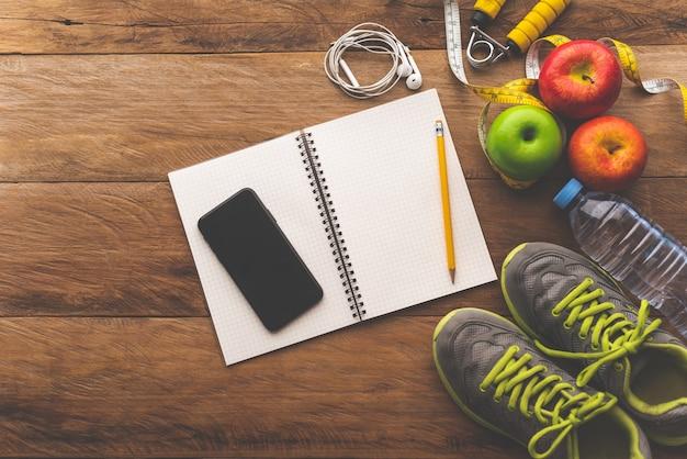 Concepto de fitness con equipo de ejercicio en mesa de madera.