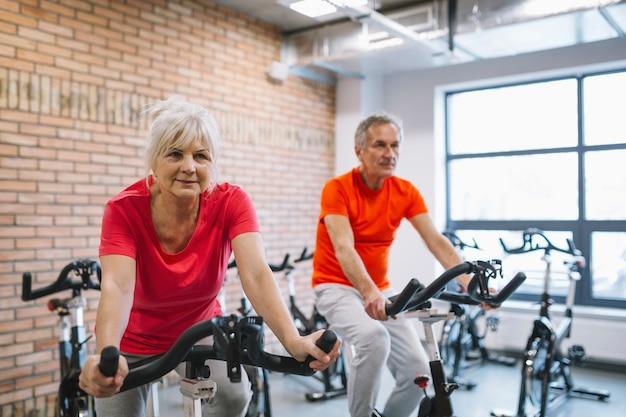 Concepto de fitness con gente mayor en bicicleta estático