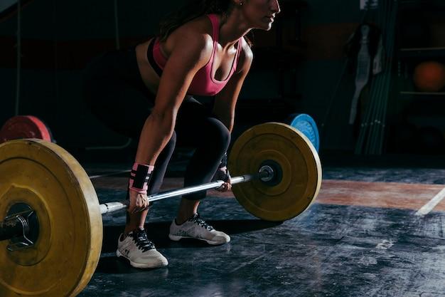 Concepto de fitness con mujer entrenando con barra de pesas