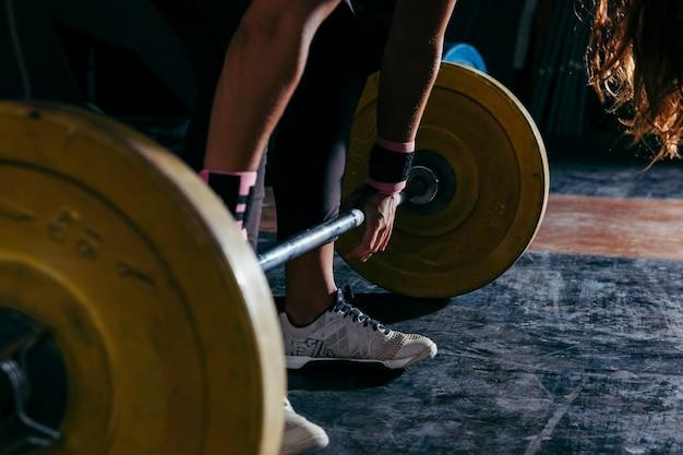 Concepto de fitness con mujer tocando barra de pesas