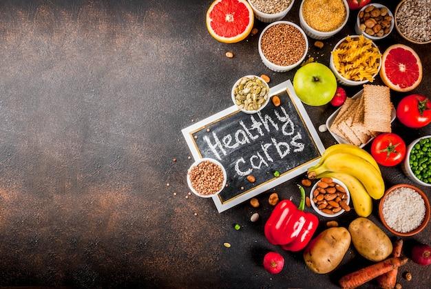 Concepto de fondo de alimentos de dieta, productos de carbohidratos saludables (carbohidratos): frutas, verduras, cereales, nueces, frijoles, espacio de copia de vista superior de fondo de hormigón azul oscuro