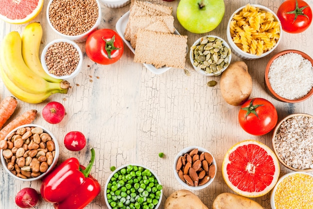 Concepto de fondo de alimentos de dieta, productos de carbohidratos saludables (carbohidratos): frutas, verduras, cereales, nueces, frijoles, marco de fondo de hormigón ligero arriba