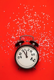 El concepto de fondo de año nuevo cambia a un reloj de alarma sobre un fondo rojo con brillo festivo ...